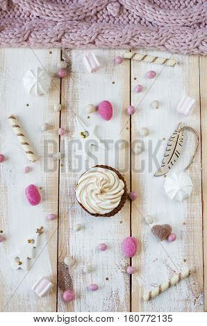Flat lay cupcake with cream on plate over candy background.