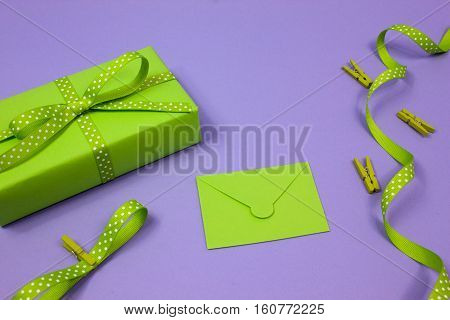 Green gift with polka dot ribbon and envelope on lilac background