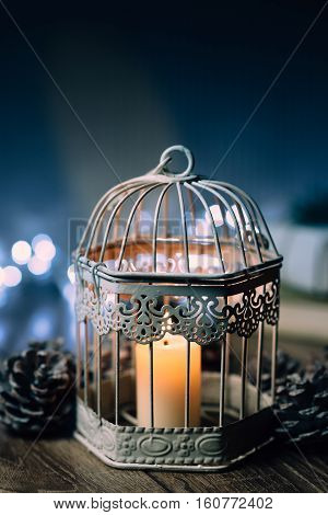 on a wooden table lighted candle in a cage on a background of luminous garlands