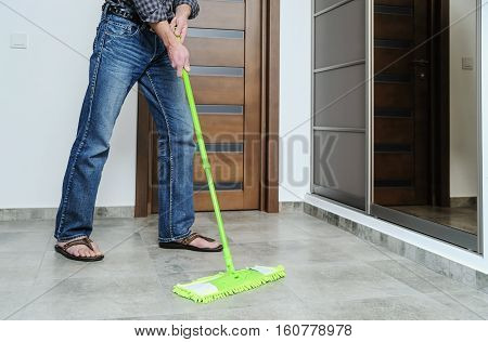 The man cleans the room. He washes the floor using a mop.