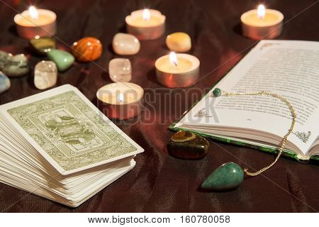 Moscow, Russia - December 4, 2016: Tarot card deck with book, green pendulum and candles. Esoteric background