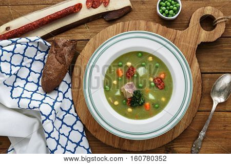 Pea soup with smoked sausage on wooden background
