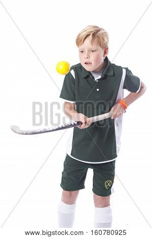 blond boy with field hockey stick and ball in studio against white background