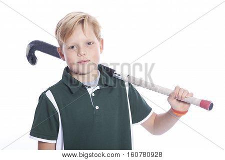 blond boy with field hockey stick in studio against white background