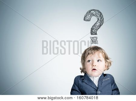 Little baby with an open mouth is wearing a blue suit and standing near a concrete wall with question mark. Mock up