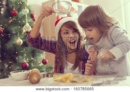 Mother and daughter making Christmas cookies and having fun. Mother sifts the flour through a sieve