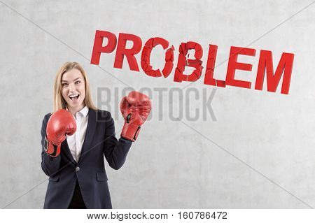 Portrait of a businesswoman boxer wearing a pair of red boxing gloves and smashing a problem word against a concrete wall.