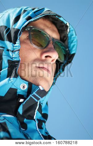 man in sunglasses and ski jacket against the blue sky