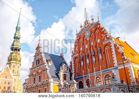 View on the central square with famous houses of Blackheads and cathedral tower in Riga city, Latvia