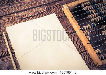 Vintage abacus envelopes and white paper on wooden table