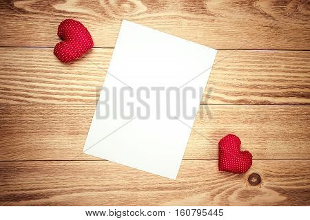 Hearts and sheet of blank paper on wooden table