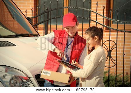 Young woman signing receipt for delivering parcel from male courier