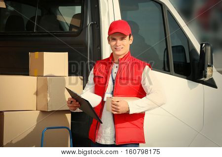 Young male courier with clipboard near delivery service van