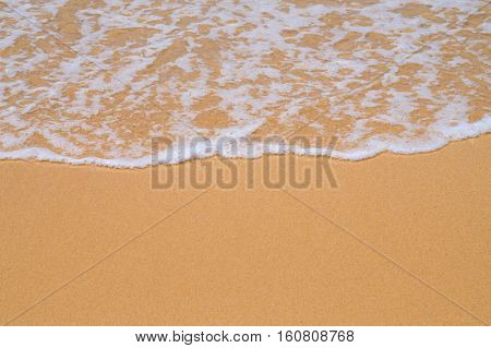 Beach yellow sand covered with wave white foam summer background. Focus is on the foam edge.