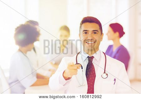 clinic, profession, people and medicine concept - happy male doctor over group of medics meeting at hospital pointing to you