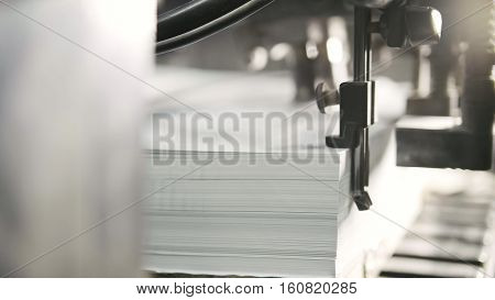 Printed sheets of paper are served in the printing press. Offset printing, CMYK, extremely close up
