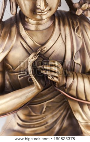 Bodkhisattva Avalokiteshvara sits in a pose of meditation arms in position Dkharmachakra mudra. He keeps stalks of flowers in finger-tips. The figure made of bronze a close up.