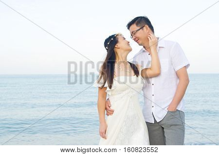 Outdoor Bride and groom on the beach in the evening.
