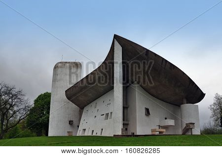 RONCHAMP, FRANCE - APRIL 23, 2016: Pilgrimage Church of Notre Dame du Haut in Ronchamp in the Vosges mountains. The facade on the background of mountain scenery. The architect is Le Corbusier. Franche-Comte, France.