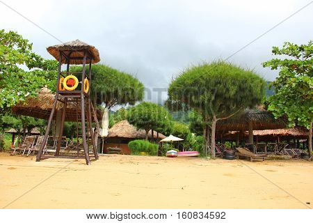 beautiful exotic beach of Vietnam, fine yellow sand, lots of greenery on the shores, coniferous and deciduous plants, a rescue tower with orange rubber rings, sun beds, parasols with straw hat