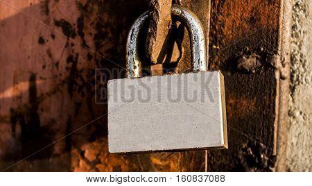 Padlock, new metal padlock on rust background, grunge padlock, metal door