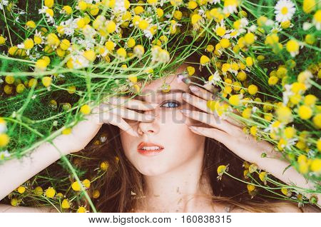 Portrait of young girl with blue eyes and freckles in chamomile field hands hiding eye
