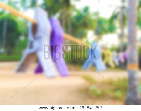 Colorful cloth pins on thread blurry background. Big wash or laundry day blurred image. Outdoor clothes washing and drying. Clothes thread in the garden. Summer countryside lifestyle photo in blur