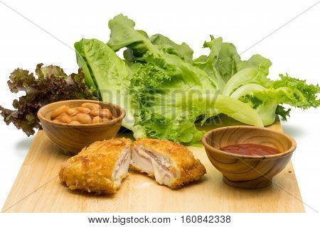 Chicken Cordon Bleu with vegetables white beans and tomato sauce on a wooden board