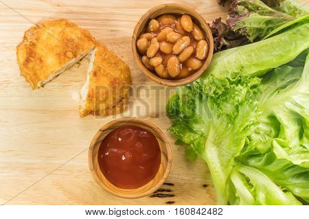 Top view of chicken cordon bleu white bean tomato sauce and vegetables on a wooden board