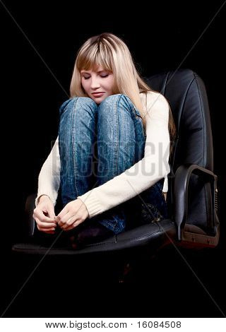 Young girl with closed eyes on chair on black background