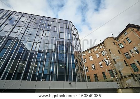The glass facade of a modern building and a historic building in Poznan