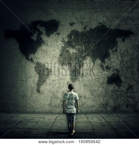 Man surrounded by limitations daily routine looking at the world map on a concrete wall. International travel cocept.