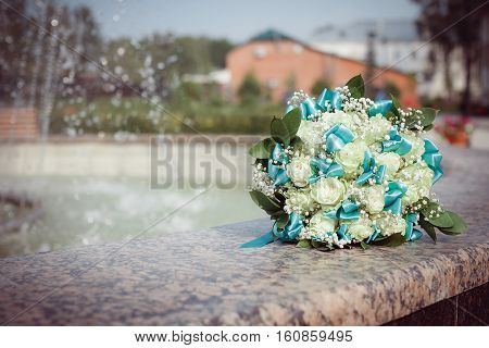 bouquet of white roses with turquoise ribbons gently lies at the fountain, wedding
