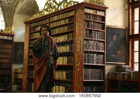A Late-Gothic wooden statue of St John the Evangelist at Strahov's monastery library in the Czech Republic. He's holding a small pouch called a girdle-book which served as a travel bag.