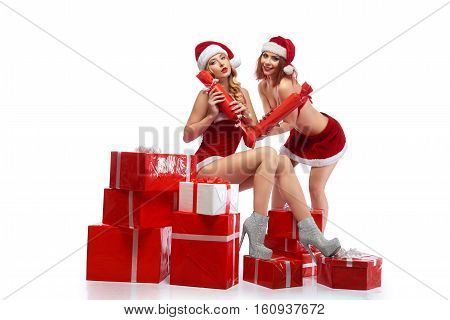 Presents for everyone. Sexy Santa girls holding presents two females in Christmas outfits posing seductively in a pile of Christmas gifts sexy Christmas concept isolated copyspace