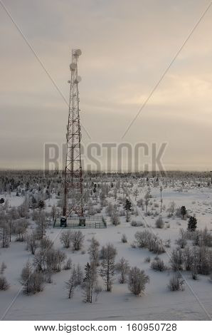 Telecommunications tower and satellite dish telecom network on evening sky with sundown and winter north forest