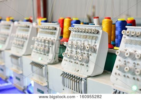 Sewing machines for embroidery. Sophisticated clothing manufacture factory
