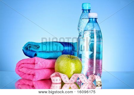Blue bottle of water, apple, sports towel and measure tape on blue background