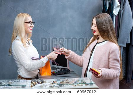 Happy woman buying clothing accessories at the paydesk with cashier in the clothing store