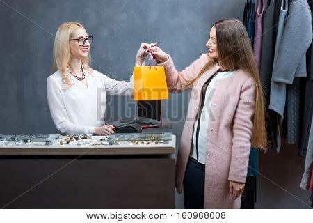 Happy cashier giving a shopping bag to the female customer at the paydesk in the clothing store