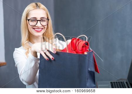 Happy cashier putting clothes into the shopping bag at the paydesk in the clothing store