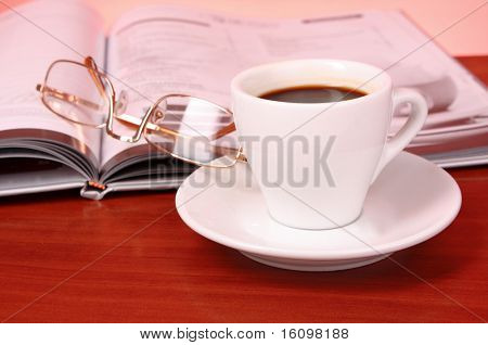 Cup of coffee, book, clock and calculator on wooden table
