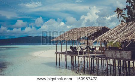 Water Hut of Homestay on Sandy Bank, Clouds in Background - Kri Island. Raja Ampat, Indonesia. West Papua