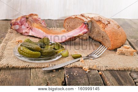 Products on an old wooden table rural style. On a napkin from a sacking bread ham on edges cucumbers and a fork lies.