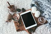 Winter homely scene, scandinavian style. Warm knit sweater, tablet pc with blank screen, candles, cu poster