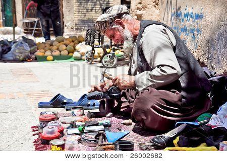SHIRAZ, IRAN - 27 APRIL: Shoemaker repairing old shoe in his street workshop shown in Shiraz, Iran on April 27, 2011.