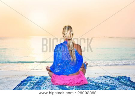 Young woman  sun gazing and meditating on tropical beach in sunrise
