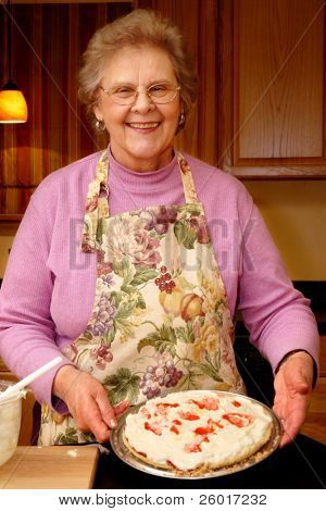 Happy senior woman displaying her no-bake cherry pie.