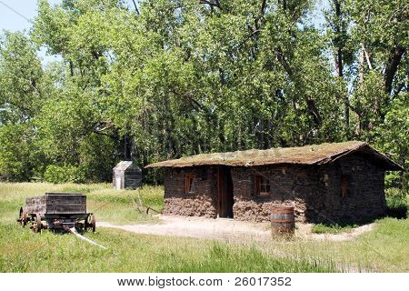 A full-scale replica of a sod hut before a stand of tall trees.   A wooden wagon, out house and barrel are nearby.