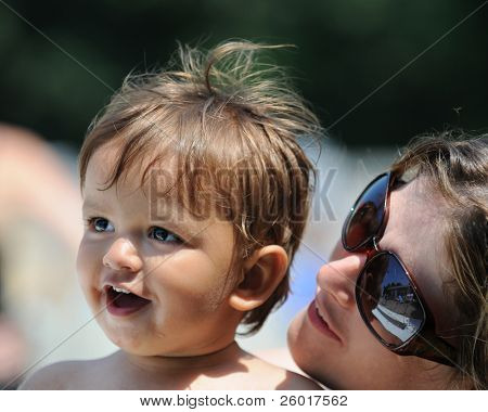 Eine Mutter, ihr Baby zu bewundern, wie sie in der Sonne sitzen.